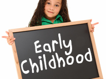 Girl holding sign that says early childhood